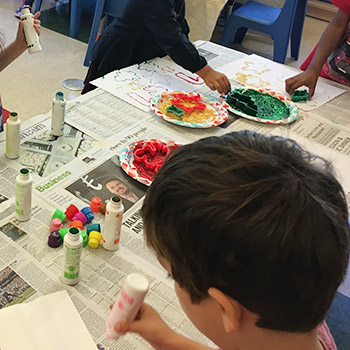 four children painting with dot paint and stamps